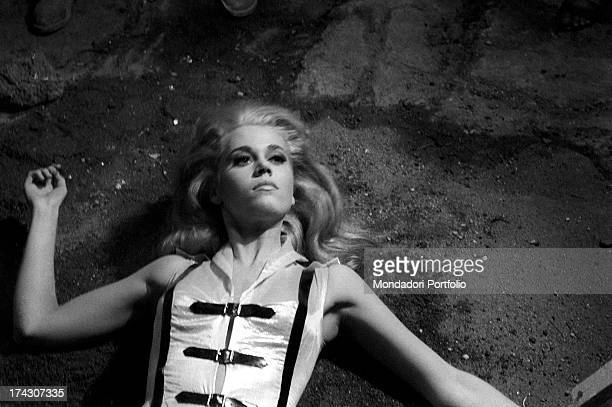 The American actress Jane Fonda wearing a clinging space suit is lying on the ground on the sandy soil of the lunar scenography she's playing the...