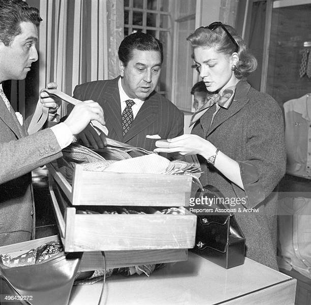 The American actress Lauren Bacall choosing a tie with the help of a salesman and of the Italian tailor Guglielmo Battistoni in his tailor's shop...