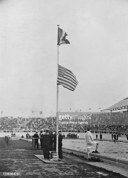The American and Italian flags being raised following the men's marathon event of the 1924 Summer Olympics, at the Stade Olympique de Colombes in...