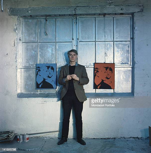 The American artist Andy Warhol posing between two of his works New York 1964