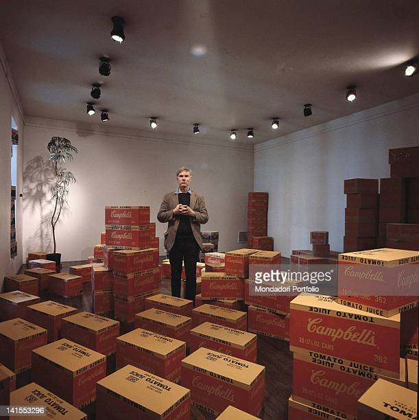 The American artist Andy Warhol posing inside his studio among cases of Campbell tomato juice New York 1964