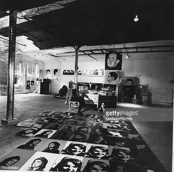 The American artist Andy Warhol sitting in his studio. Some paintings depict Jacqueline Kennedy. New York, 1964
