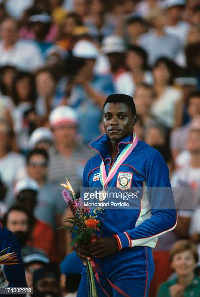 The American athlete Carl Lewis born Frederick Carlton Lewis holding a bunch of flowers in his hands looks satisfied at the stands during the...