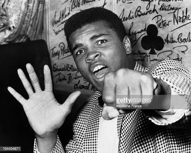 The American boxer Cassius CLAY arriving in London for a match with a British opponent Henry COOPER He is showing his fist and five fingers...
