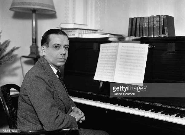 The American composer and lyricist Cole Porter sits at the piano