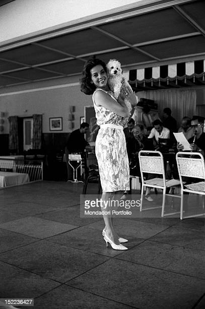 The American dancer and actress Abbe Lane smiling and holding in her arms her poodle Madrid 1963