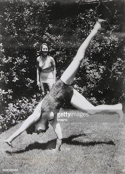 The American film actress Norma Shearer is doing cartwheels in her garden in Hollywood She is being watched by her colleague Merle Oberon 1936...
