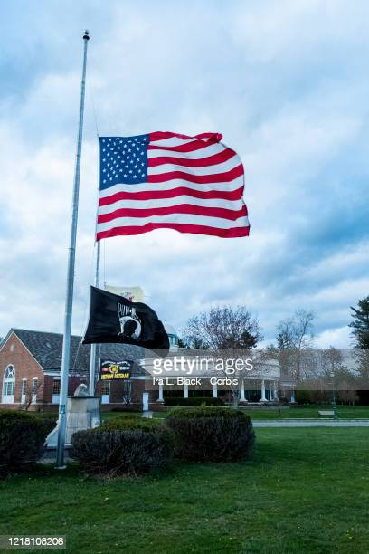 The American flag a POW flag a Vietnam War flag and the the flag of the State of NJ all fly at halfmast in front of the library in Livingston NJ on...