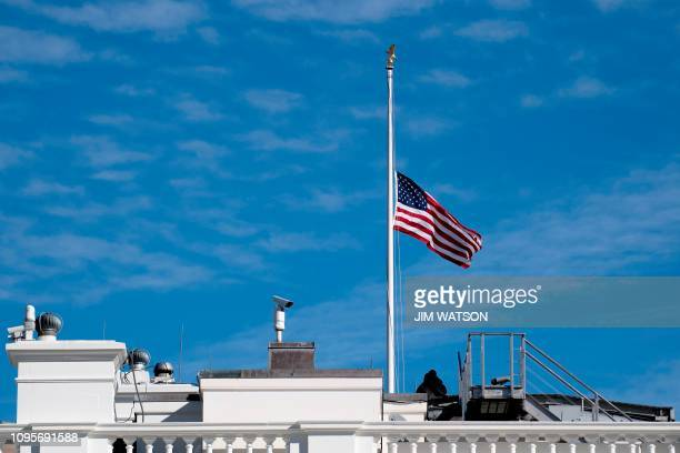 The American Flag above the White House is lowered to half mast to honor the life and legacy of former Congressman John Dingell in Washington DC on...