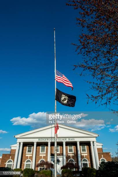 The American flag and the POW MIA flag fly at half mast outside the Ridgewood Village Hall building. Photographed in Ridgewood, NJ, USA on April 15,...