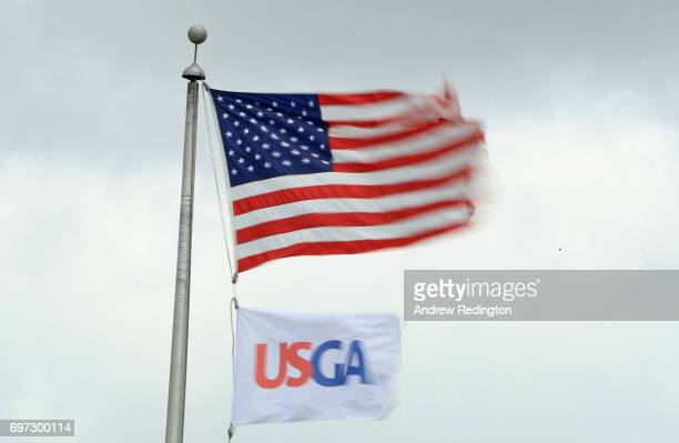 The American flag and USGA flags fly in the wind during the final round of the 2017 US Open at Erin Hills on June 18 2017 in Hartford Wisconsin