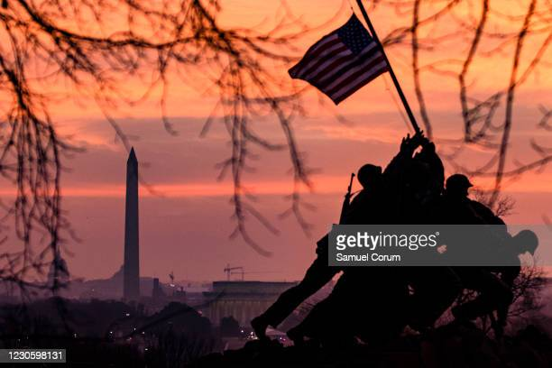 The American flag flies above the US Marine Corps War Memorial, also known as the Iwo Jima Memorial, with the Washington Monument in the distance on...