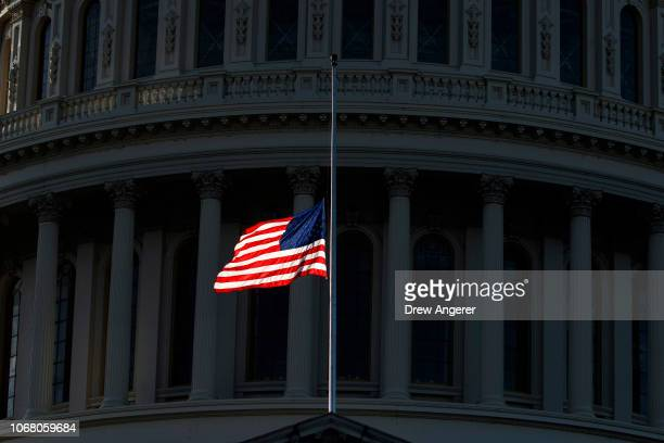 The American flag flies at halfstaff ahead of the arrival of the casket of the late former President George HW Bush at the US Capitol December 3 2018...
