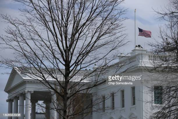 The American flag flies at half-staff at the White House in honor of the victims of Monday's mass shooting in Boulder, Colorado, on March 23, 2021 in...
