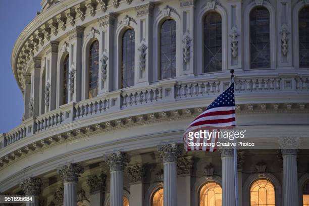 the american flag flies outside the u.s. capitol before sunrise - capitólio capitol hill - fotografias e filmes do acervo