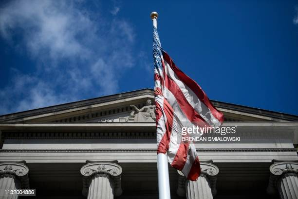 The American flag flies outside the US Department of Justice March 22 2019 in Washington DC US President Donald Trump went on air Friday to double...