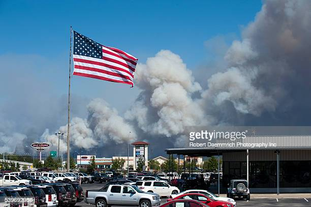 The American flag flies over a parking lot in Bastrop Texas with the smoke of an outofcontrol wildfire billowing skyward in the background Officials...