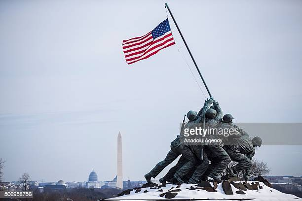 The American Flag flies over the snow covered Marine Corps Iwo Jima War Memorial with the Washington Monument and US Capitol in the distance in...