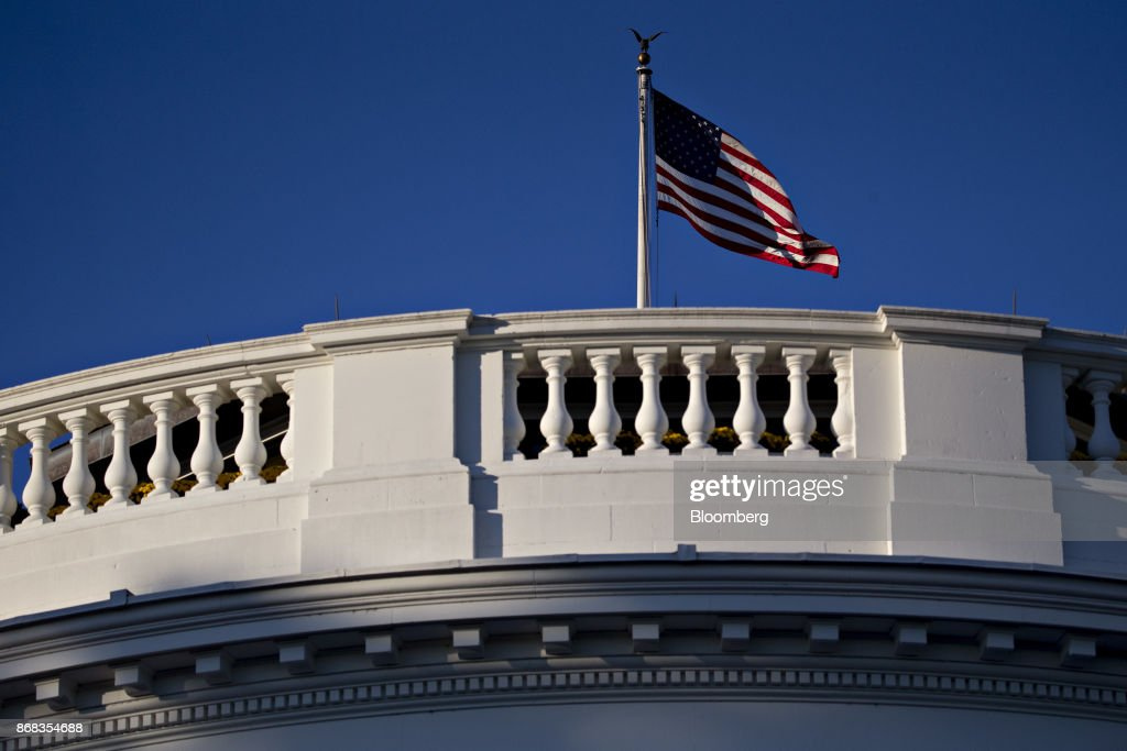 The American flag flies over the White House in Washington, D.C., U.S., on Monday, Oct. 30, 2017. President Donald Trump greeted costumed children during a traditional Halloween trick-or-treat at the White House, on the same day as Special Counsel Robert Mueller's investigation took a major turn as authorities charged three people -- a former campaign chief, his business associate and an ex-policy adviser -- with crimes including money laundering, lying to the FBI and conspiracy. Photographer: Andrew Harrer/Bloomberg via Getty Images