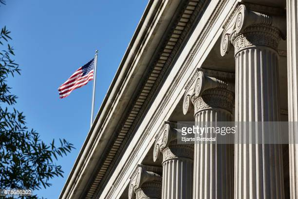 the american flag flying over the treasury department - monetary policy stock pictures, royalty-free photos & images