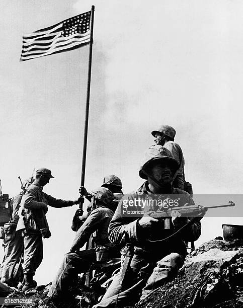 The American flag is carried by Marines of 28th regiment 5th Div. To summit of Mt. Suribachi, Iwo Jima in volcano Islands and hoisted to top of...