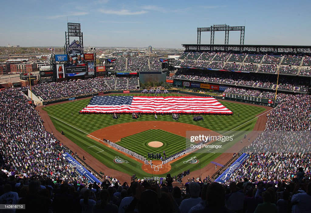 The American Flag is displayed on the field as the national anthem is observed prior to the game between the San Francisco Giants and the Colorado Rockies on Opening Day at Coors Field on April 9, 2012 in Denver, Colorado.