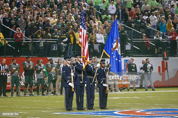 The American flag is held during the nation anthem before the Motel 6 Cactus Bowl college football game between the Boise State Broncos and the...