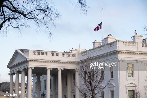 The American flag is seen at half staff over the White House in Washington, DC, February 22 in honor of the 500,000 lives lost to coronavirus in the...
