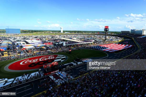 The American flag is unfurled along the front stretch of Charlotte Motor Speedway during prerace festivities for the CocaCola 600 on Sunday May 28...