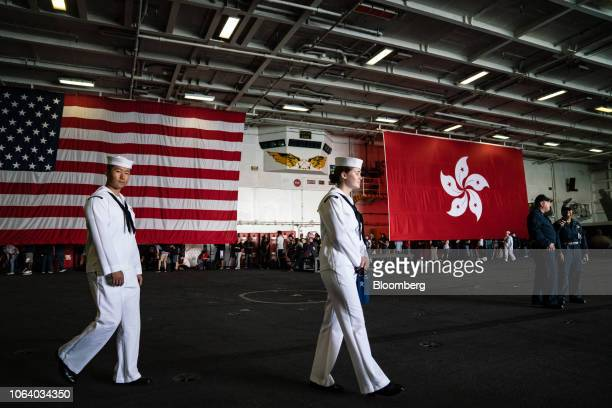 The American flag, left, and the Hong Kong Special Administrative Region flag hang on board the USS Ronald Reagan, a Nimitz-class aircraft carrier...