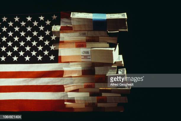 The American flag superimposed over a pile of American dollars banknotes, US, 1982.