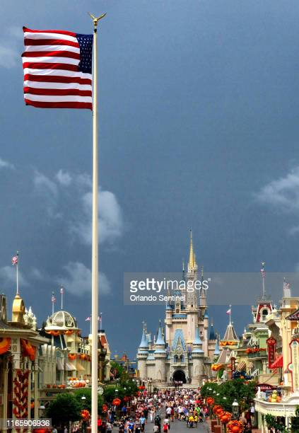 The American flag whips in the wind shortly before the Magic Kingdom at Walt Disney World in Lake Buena Vista, Fla., closed early due to weather...