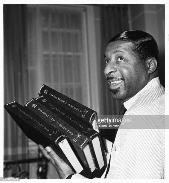 The American jazz pianist and composer Erroll Garner holding a pile of telephone directories