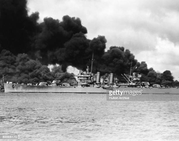 The American light cruiser USS Phoenix passing the burning USS West Virginia and USS Arizona, during the Japanese attack on Pearl Harbor, 7TH...