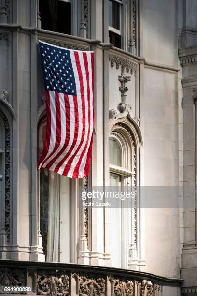 The American National Flag is hoisted at buildings wall at Fifth Avenue Uptown Manhattan in New York City.