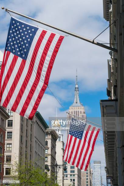 The American National Flags are hoisted among the Fifth Avenue in New York City. Empire State Building can be seen behind in the clouds.