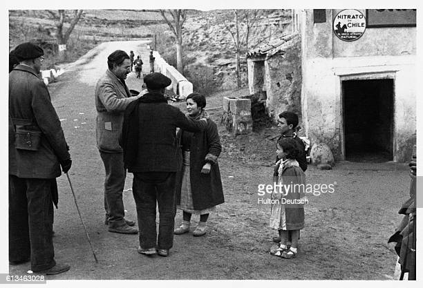 The American novelist and war correspondant Ernest Hemingway talks to a woman refugee and two children made homeless by the Spanish Civil War