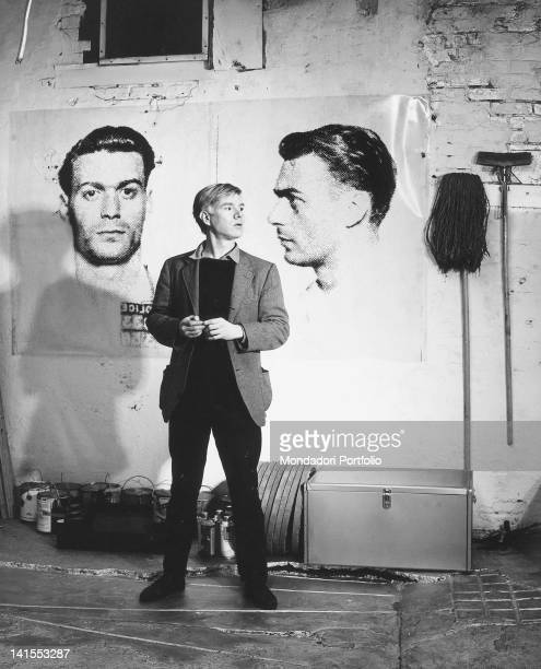 The American painter and director Andy Warhol posing in his studio in front of two portraits inspired by mug shots New York 1964