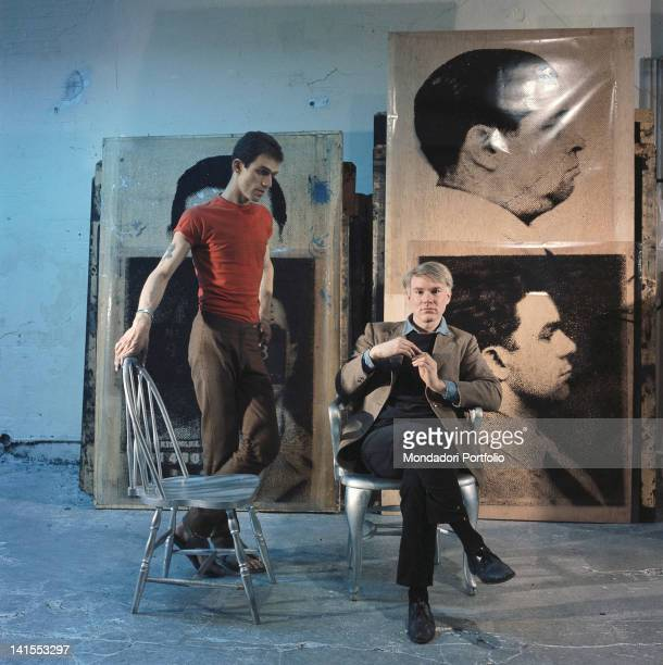 The American painter and director Andy Warhol posing in his studio in front of four portraits inspired by mug shots. New York, 1964