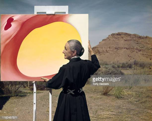 1960 The American painter Georgia O'Keeffe is standing outside her art studio holing her pelvis series color painting that has center yellow and...