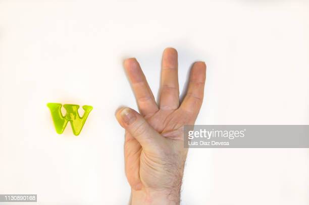 the american sign language for the letter w. - menschlicher finger stock-fotos und bilder