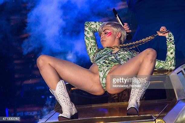 The American singer Miley Cyrus in concert at Mediolanum Forum while dancing with her legs open in a provocative pose lying on a car She wears a...