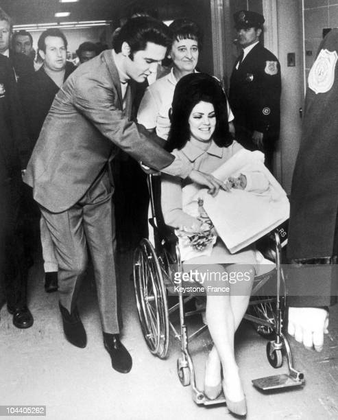 The American singer/actor Elvis PRESLEY walking beside his wife Priscilla, pictured carrying their newborn daughter Lisa Marie, on February 10, 1968.