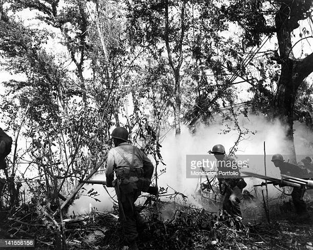 The American soldiers of the Sixth Division advancing in the forest on the Philippines island of Luzon, protected by a smokescreen. Luzon, March 1945