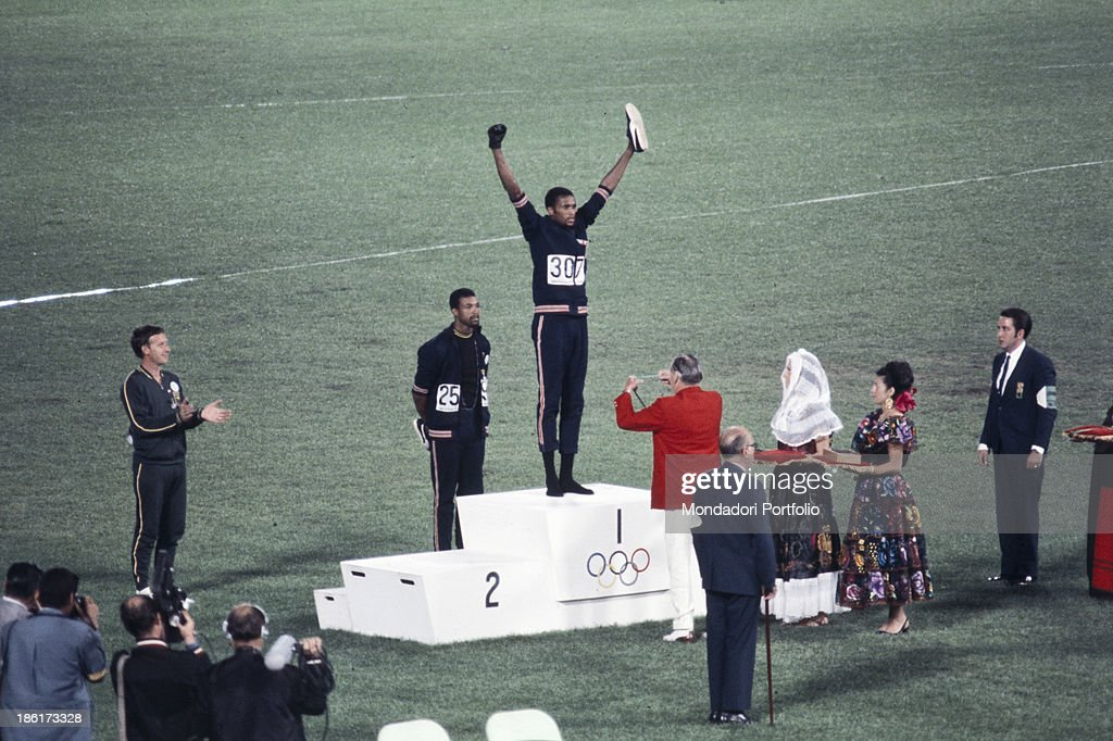 The american sprinters Tommie Smith, John Carlos and Peter Norman during the award ceremony of the 200 m's race at the Mexican Olympic games. During the awards ceremony, Smith and Carlos protested against racial discrimination: they went barefoot on the podium and listened to their anthem bowing their heads and raising a fist with a black glove. Mexico City, Mexico, 1968 Mexico city, Mexico, 1968.
