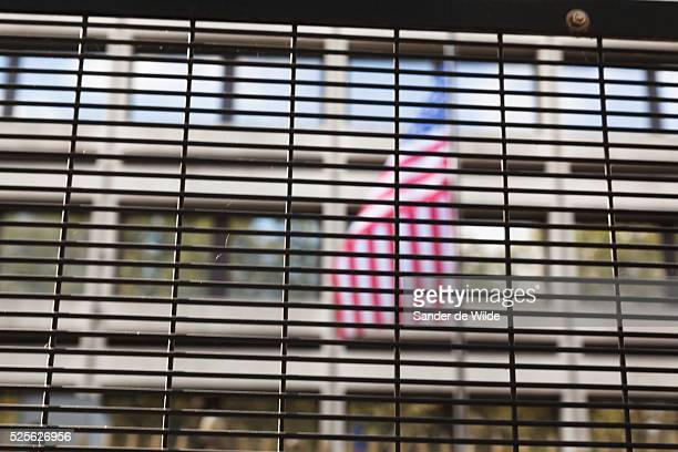 The American stars and stripes flag on the American Embassy in Brussel, shot through a high fence surrounding the Embassy