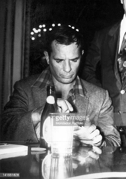 The American writer Jack Kerouac sitting at a table with a bottle of beer Naples 1970s