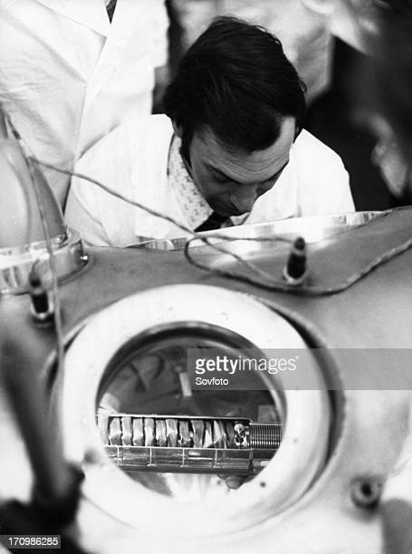 The ampule containing lunar soil and rock delivered by the reentry module of the soviet lunar lander luna 24 is being examined in a vacuum chamber by...