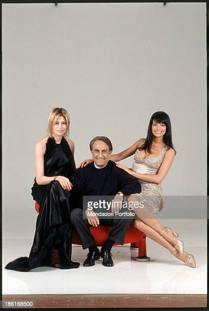The anchorman Emilio Fede is seated on a red armchair and is smiling next to two showgirls Elenoire Casalegno and Natalia Estrada both seated on the...