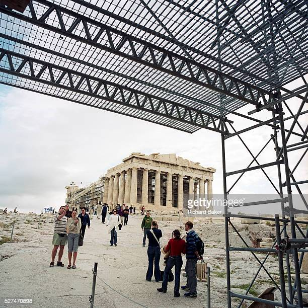 The ancient Parthenon sits on Acropolis hill surrounded by global tourists and scaffolding Here the modern world's philosophy was born once the...